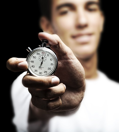 artifact: portrait of young man holding a vintage timer against a black background