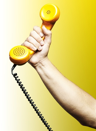 hand holding a yellow vintage telephone over yellow background photo
