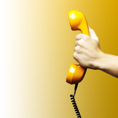 phone conversations: Hand holding vintage telephone receiver isolated over yellow background Stock Photo