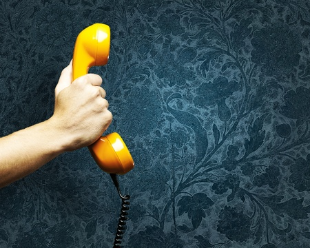 ancient telephone: hand holding a vintage telephone against a grunge background