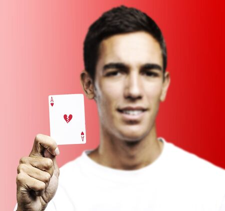 young man showing a poker card with broken hearth against a red background photo