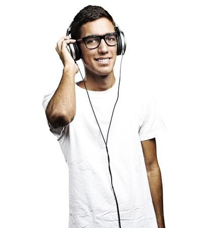 personas escuchando: Retrato de hombre con gafas y audífonos escuchando música sobre un fondo blanco Foto de archivo