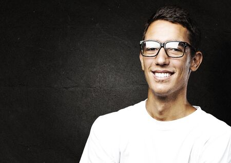 portrait of young man with glasses against a grunge background photo