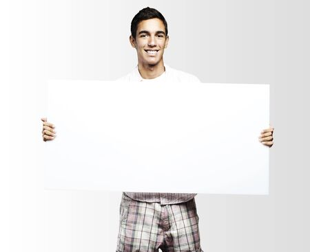 young man smiling and showing a big banner against a grey background photo