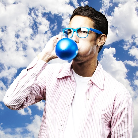 portrait of young man inflating a blue balloon against a sky background photo