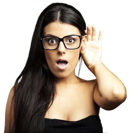 portrait of young woman with glasses hearing something over yellow background photo