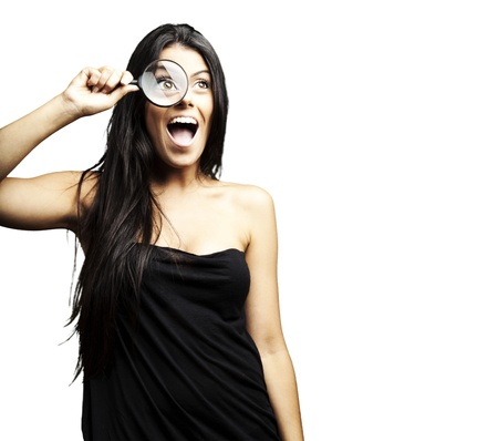 portrait of woman excited looking through a magnifying glass over white background photo
