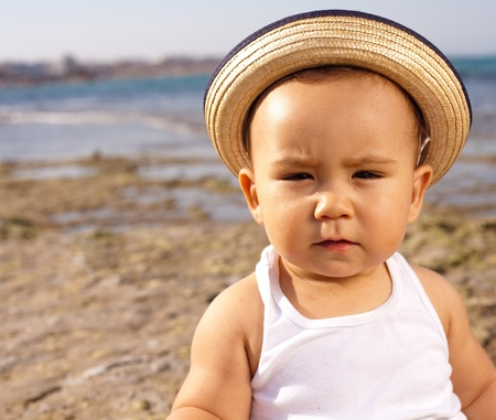 baby with a straw hat in the beach photo