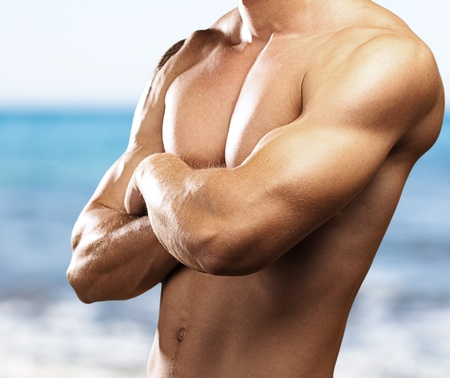 muscle arm: strong torso of young man against a sea background