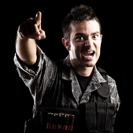 portrait of young soldier shouting and pointing with the hand against a black background photo