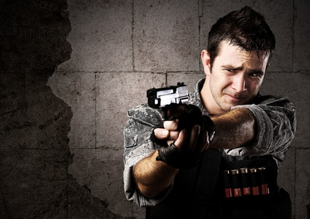 man holding gun: portrait of young soldier aiming with gun against a grunge bricks wall