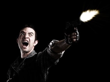 gangster with gun: man shooting on a black background Stock Photo