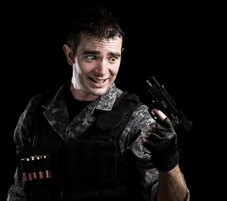 man holding gun: young soldier without ammunition of pistol on black background Stock Photo