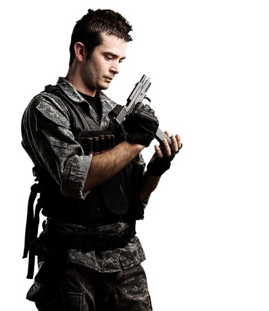 kill: portrait of young soldier reloaing his gun against a white background