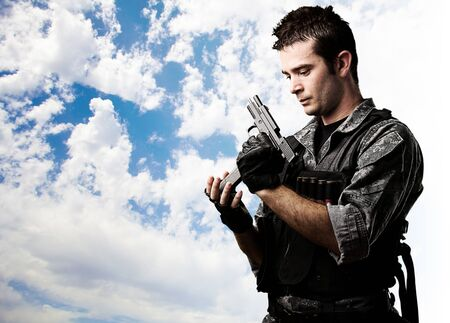 reloading: portrait of young soldier reloading the gun against a cloudy sky background