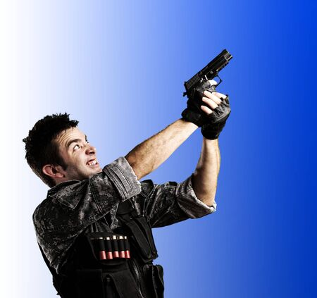 portrait of young soldier shooting with a gun against a white background photo
