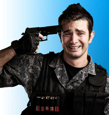 portrait of young soldier suiciding against a blue background photo