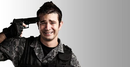 portrait of young soldier suiciding against a grey background photo