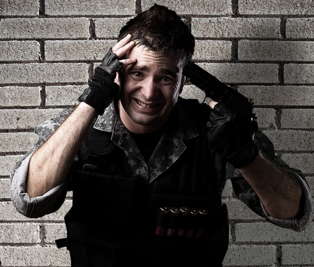 young soldier pointing himself with a pistol against a bricks background photo