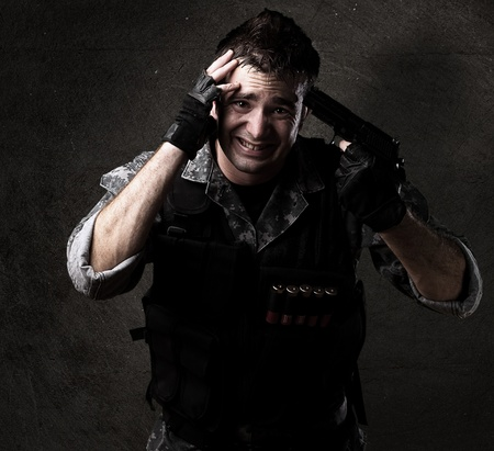 young soldier pointing himself with a pistol against a grunge background photo