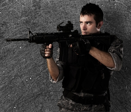 military training: young soldier pointing a target against a grunge wall Stock Photo
