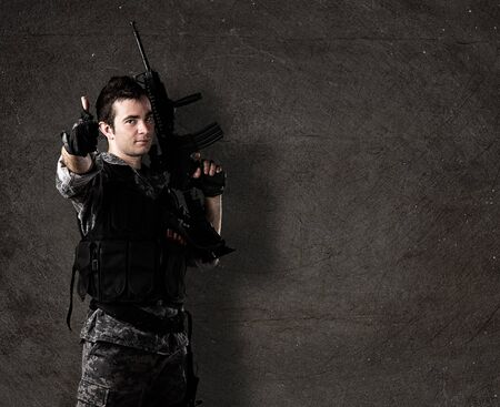 iraq war: young soldier with rifle with finger up against a grunge wall