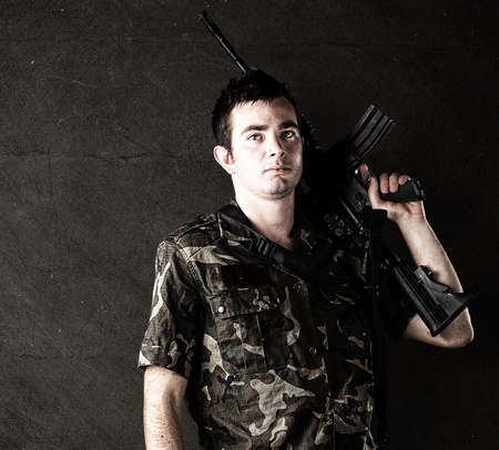 young soldier with assault rifle against a grunge wall photo