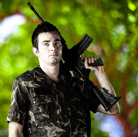 portrait of young soldier with rifle and jungle camouflage against a nature background photo