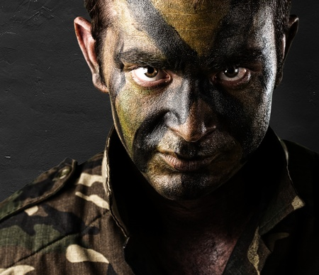 young soldier face with jungle camouflage against a grunge wall photo
