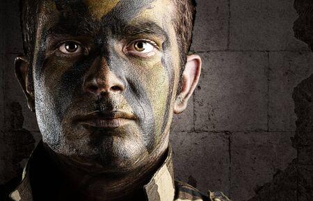 target thinking: retrato de la cara de joven soldado pintados con camuflaje de selva contra una pared de ladrillos del grunge Foto de archivo