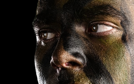 face guard: young soldier face with jungle camouflage on black background