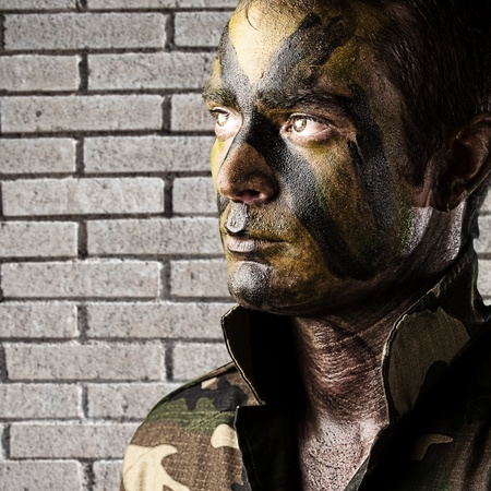 portrait of young soldier face painted with jungle camouflage against a grunge bicks wall photo
