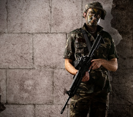 portrait of young soldier with jungle camouflage holding a rifle against a grunge bricks wall photo