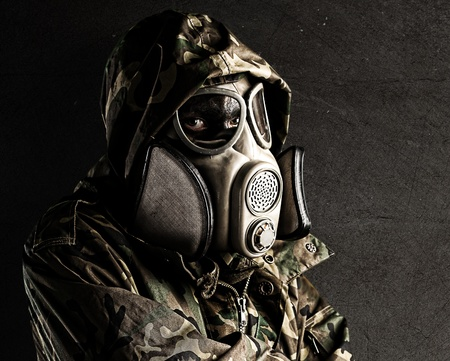 antique rifle: portrait of young soldier with gas mask against a grunge background