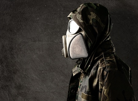 vintage military rifle: portrait of young soldier with gas mask against a grunge background
