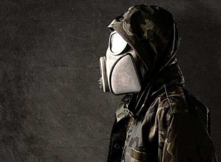 mascara de gas: Retrato de joven soldado con máscara de gas contra un fondo grunge