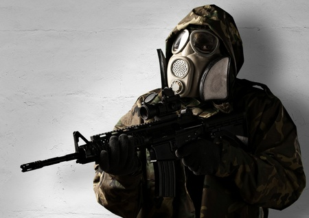armed soldier with gas mask wearing a camouflage uniform against a wall photo