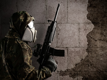 soldier with camouflage suit and gas mask against a grunge bricks wall Stock Photo - 10973991