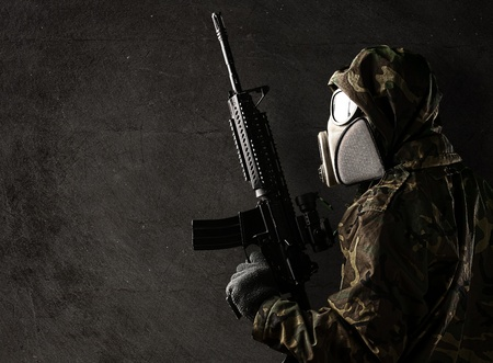 soldier with camouflage suit and gas mask against a grunge background Stock Photo - 10973996