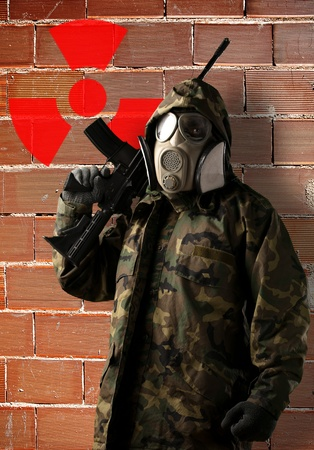 portrait of soldier with camouflage and gas mask against grunge bricks wall with radioactive symbol photo