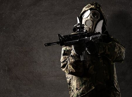 portrait of soldier with rifle and gas mask against a grunge background photo