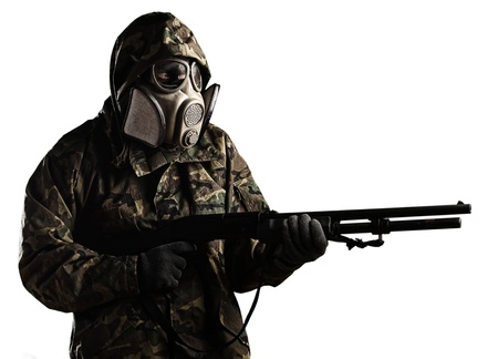 gas mask: portrait of young soldier aiming with rifle against a black background Stock Photo