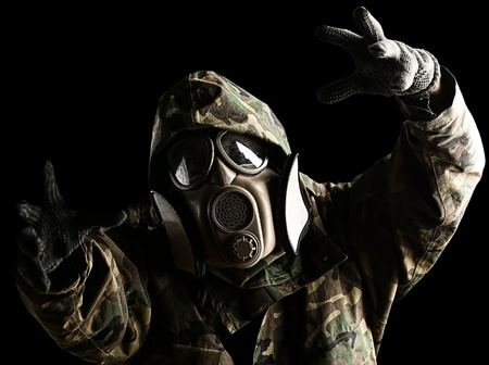 portrait of soldier with jungle camouflage and gas mask trying to hold something over black Stock Photo - 10973834