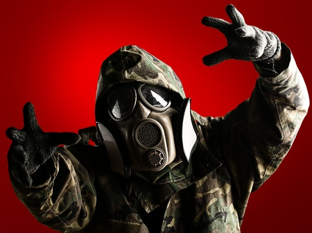 portrait of soldier with jungle camouflage and gas mask trying to hold something over red photo
