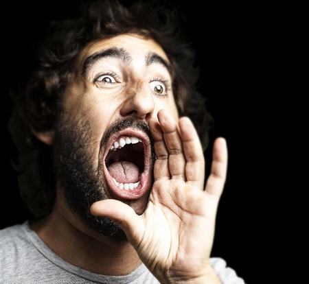 jonge man schreeuwen tegen een zwarte achtergrond Stockfoto