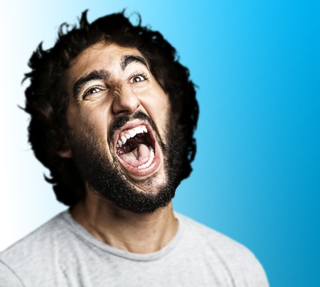 young man shouting against a blue background  photo