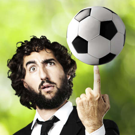 portrait of young man playing with a soccer ball against a park background photo