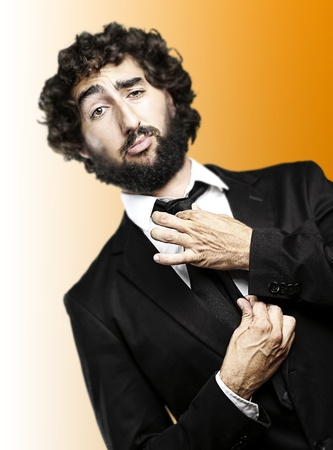 portrait of young man adjusting his suit against a orange background photo