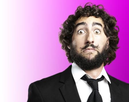gente loca: retrato de hombre joven frente a miedo en contra de un fondo de color rosa Foto de archivo