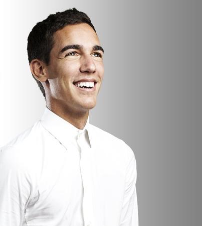 sparo: Ritratto di giovane uomo con camicia bianca sorridente su uno sfondo grigio